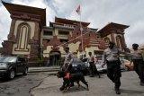 Anggota Unit Satwa K9 Polda Bali melakukan patroli pada masa perpanjangan Pemberlakuan Pembatasan Kegiatan Masyarakat (PPKM) di Pasar Badung, Denpasar, Bali, Rabu (27/1/2021). Pemerintah Provinsi Bali memperketat PPKM jilid 2 dengan memajukan pembatasan jam operasional dari pukul 21.00 WITA menjadi pukul 20.00 WITA mulai Selasa (26/1/2021) hingga Senin (8/2/2021) mendatang. ANTARA FOTO/Nyoman Hendra Wibowo/nym.