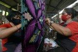 Perajin menyelesaikan pembuatan kain Endek atau kain khas Bali dengan menggunakan alat tenun tradisional di Sentra Kerajinan Tenun Ikat Sekar Jepun, Denpasar, Bali, Kamis (28/1/2021). Pemerintah Provinsi Bali mengharapkan Gerakan Nasional Bangga Buatan Indonesia (Gernas BBI) 2021 menjadi momentum untuk memperkenalkan produk-produk asli Bali ke mancanegara dengan memanfaatkan pemasaran melalui daring atau