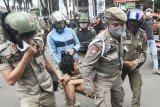 Sejumlah petugas Satpol PP mengamankan seorang Penyandang Masalah Kesejahteraan Sosial (PMKS), di Jalan Ir Juanda, Bekasi, Jawa Barat, Kamis (28/1/2021). Pemerintah setempat menggalakkan penertiban PMKS yang berkeliaran saat Pemberlakuan Pembatasan Kegiatan Masyarakat (PPKM) untuk mencegah penyebaran COVID-19. ANTARA FOTO/Fakhri Hermansyah/hp.