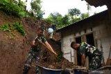 Petugas gabungan membersihkan reruntuhan tanah longsor di Desa Kepel, Kare, Kabupaten Madiun, Jawa Timur, Kamis (4/2/2021). Hujan deras yang terjadi di wilayah tersebut pada Rabu (3/2) malam mengakibatkan tanah longsor yang menimpa rumah warga. Antara Jatim/Siswowidodo/zk