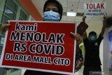 Sejumlah orang yang mengatasnamakan Perkumpulan Penghuni Pemilik dan Pedagang (P4) Cito melakukan aksi bentang poster di City of Tomorrow (Cito) Mall, Surabaya, Jawa Timur,  Rabu (3/2/2021). Mereka menolak rencana pembukaan rumah sakit rujukan bagi pasien COVID-19 yang berada di dekat mall tersebut. Antara Jatim/Didik/Zk