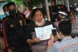 Warga terdampak pandemi COVID-19 mencairkan Bantuan Sosial Tunai (BST) tahap kedua di halaman kantor Pos, Kota Kediri, Jawa Timur, Jumat (5/2/2021). Data dari Dinas Sosial daerah setempat penerima BST tahap kedua meningkat menjadi 11.500 keluarga penerima manfaat (KPM) dibanding tahap pertama sebanyak 10.785 KPM. Antara Jatim/Prasetia Fauzani/ZK