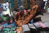 Pedagang menunggui batik dagangannya di Pasar Batik Tradisional, Pamekasan, Jawa Timur, Minggu (7/2/2021). Kebijakan Pemkab Pamekasan yang memberlakukan pakaian adat Madura, Baju Koko dan Batik Pamekasan, sebagai seragam Pegawai Negeri Sipil (PNS) dan non pegawai PNS disambut gembira oleh pelaku batik di daerah itu. Antara Jatim/Saiful Bahri/zk.