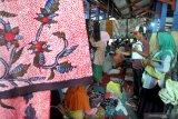 Pedagang batik dan pembeli  bertransaksi batik di Pasar Batik Tradisional, Pamekasan, Jawa Timur, Minggu (7/2/2021). Kebijakan Pemkab Pamekasan yang memberlakukan pakaian adat Madura, Baju Koko dan Batik Pamekasan, sebagai seragam Pegawai Negeri Sipil (PNS) dan non pegawai PNS disambut gembira oleh pelaku batik di daerah itu. Antara Jatim/Saiful Bahri/zk.