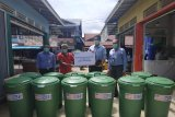 Pimpinan Cabang BRI Putussibau Purnama Pakualam menyerahkan bantuan program BRI Peduli CSR kepada Ketua RT 05 Pasar Pagi Putussibau sebagai wujud kepedulian BRI Putussibau dalam upaya penanggulangan pandemi COVID-19 di daerah tersebut, pada Senin (8/2/2021). FOTO ANTARA/Timotius