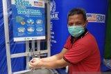 Ketua RT 05/RW 01 Pasar Pagi Putussibau Apeng mempraktekan cuci tangan sebagai bentuk penerapan protokol kesehatan di Pasar Pagi Putussibau dari bantuan CSR BRI Cabang Putussibau. FOTO ANTARA/Timotius