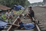 Sejumlah warga pengungsi banjir beristirahat di lintasan rel kereta yang tidak terpakai di Desa Waringinjaya, Cikarang, Kabupaten Bekasi, Jawa Barat, Selasa (9/2/2021). Menurut warga, para mereka sudah tiga hari berada di pengungisan akibat rumah yang masih tergenang banjir luapan sungai Citarum dan Cibe'et. ANTARA FOTO/Fakhri Hermansyah/hp.