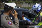 Petugas Kepolisian memeriksa surat keterangan sehat dari pengendara yang keluar di Gerbang Tol Cileunyi, Kabupaten Bandung, Jawa Barat, Kamis (11/2/2021). Pemeriksaan yang dilakukan kepada pengendara dari luar Kota Bandung tersebut digelar dalam rangka penerapan pembatasan kegiatan masyarakat (PPKM) berskala mikro guna mewujudkan Kabupaten Bandung zona hijau dari COVID-19. ANTARA JABAR/Raisan Al Farisi/agr