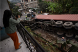 Warga memotret proses evakuasi truk kontainer bermuatan tepung kelapa yang terguling di jalan raya Bandung-Tasikmalaya, Malangbong, Kabupaten Garut, Jawa Barat, Kamis (11/2/2021). Kecelakaan truk tersebut diduga karena rem blong dan tidak ada korban jiwa dalam peristiwa tersebut. ANTARA FOTO/Candra Yanuarsyah/agr/aww.
