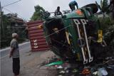 Warga melihat kondisi truk kontainer bermuatan tepung kelapa yang terguling di jalan raya Bandung-Tasikmalaya, Malangbong, Kabupaten Garut, Jawa Barat, Kamis (11/2/2021). Kecelakaan truk tersebut diduga karena rem blong dan tidak ada korban jiwa dalam peristiwa tersebut. ANTARA FOTO/Candra Yanuarsyah/agr/aww.