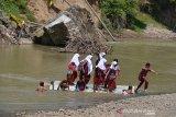 MURID GUNAKAN RAKIT BAMBU SEBERANGI SUNGAI DI PEDALAMAN ACEH. Sejumlah murid sekolah dasar menggunakan rakit dari bambu menyeberangi sungai saat pulang sekolah di Desa Siron Krueng, Kecamatan Kuta Cot Glee, Kabupaten Aceh Besar, Aceh, Rabu (17/2/2021). Pascaputusnya jembatan gantung diterjang banjir sekitar lima tahun lalu, murid sekolah dasar terpaksa menyeberangi sungai menggunakan rakit dengan mendapat pengawalan ketat orang tua mereka dan selain kekhawatiran keselamatan anak mereka pascapenangkapan dua ekor buaya oleh petugas Balai Konservasi Sumber Daya Alam (BKSDA) pertengah tahun 2020 di sungai tersebut. ANTARA FOTO/Ampelsa.