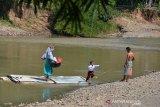 MURID SEBERANGI SUNGAI DENGAN RAKIT BAMBU DI PEDALAMAN ACEH. Warga bersama anaknya menggunakan rakit dari bambu menyeberangi sungai saat pulang sekolah di Desa Siron Krueng, Kecamatan Kuta Cot Glee, Kabupaten Aceh Besar, Aceh, Rabu (17/2/2021). Pascaputusnya jembatan gantung diterjang banjir sekitar lima tahun lalu, murid sekolah dasar terpaksa menyeberangi sungai menggunakan rakit dengan mendapat pengawalan ketat orang tua mereka dan selain kekhawatiran keselamatan anak mereka pascapenangkapan dua ekor buaya oleh petugas Balai Konservasi Sumber Daya Alam (BKSDA) pertengah tahun 2020 di sungai tersebut. ANTARA FOTO/Ampelsa.