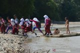 MURID SEBERANGI SUNGAI DENGAN RAKIT BAMBU DI PEDALAMAN ACEH. Sejumlah murid sekolah dasar menggunakan rakit dari bambu menyeberangi sungai saat pulang sekolah di Desa Siron Krueng, Kecamatan Kuta Cot Glee, Kabupaten Aceh Besar, Aceh, Rabu (17/2/2021). Pascaputusnya jembatan gantung diterjang banjir sekitar lima tahun lalu, murid sekolah dasar terpaksa menyeberangi sungai menggunakan rakit dengan mendapat pengawalan ketat orang tua mereka dan selain kekhawatiran keselamatan anak mereka pascapenangkapan dua ekor buaya oleh petugas Balai Konservasi Sumber Daya Alam (BKSDA) pertengah tahun 2020 di sungai tersebut. ANTARA FOTO/Ampelsa.