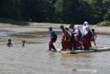 MURID SEBERANGI SUNGAI DENGAN RAKIT BAMBU DIPEDALAMAN ACEH. Sejumlah murid sekolah dasar menggunakan rakit dari bambu menyeberangi sungai saat pulang sekolah di Desa Siron Krueng, Kecamatan Kuta Cot Glee, Kabupaten Aceh Besar, Aceh, Rabu (17/2/2021). Pascaputusnya jembatan gantung diterjang banjir sekitar lima tahun lalu, murid sekolah dasar terpaksa menyeberangi sungai menggunakan rakit dengan mendapat pengawalan ketat orang tua mereka dan selain kekhawatiran keselamatan anak mereka pascapenangkapan dua ekor buaya oleh petugas Balai Konservasi Sumber Daya Alam (BKSDA) pertengah tahun 2020 di sungai tersebut. ANTARA FOTO/Ampelsa.
