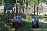 MURID SEBERANGI SUNGAI DENGAN RAKIT BAMBU DIPEDALAMAN ACEH. Sejumlah murid sekolah dasar melintas dekat papan pengumumam bertuliskan kawasan habitat buaya seusai menyeberangi sungai menggunakan rakit sepulang sekolah di Desa Siron Krueng, Kecamatan Kuta Cot Glee, Kabupaten Aceh Besar, Aceh, Rabu (17/2/2021). Pascaputusnya jembatan gantung diterjang banjir sekitar lima tahun lalu, murid sekolah dasar terpaksa menyeberangi sungai menggunakan rakit dengan mendapat pengawalan ketat orang tua mereka dan selain kekhawatiran keselamatan anak mereka pascapenangkapan dua ekor buaya oleh petugas Balai Konservasi Sumber Daya Alam (BKSDA) pertengah tahun 2020 di sungai tersebut. ANTARA FOTO/Ampelsa.