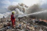 Petugas berusaha memadamkan api di Tempat Pembuangan Akhir (TPA) Punggur, Batam, Kepulauan Riau (Kepri), Selasa (16/2/2021). Petugas kesulitan melakukan pemadaman karena banyaknya bahan yang mudah terbakar disertai angin kencang. ANTARAFOTO/Teguh Prihatna/Lmo/rwa.
