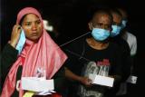 Sejumlah Pekerja Migran Indonesia (PMI) berbaris untuk menjalani pendataan setibanya di Dinas Sosial Provinsi Kalbar di Pontianak, Kalimantan Barat, Rabu (17/2/2021) malam. BP2MI Pontianak mencatat terdapat 160 PMI (131 pria, 29 wanita) bermasalah yang dideportasi Pemerintah Malaysia melalui PLBN Entikong karena tidak memiliki paspor dan dokumen kerja, melanggar PSBB serta terlibat kasus kriminal. ANTARA FOTO/Jessica Helena Wuysang/foc.