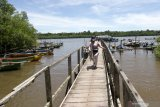 Wisatawan menikmati  suasana jembatan hutan mangrove di Bedul, Taman Nasional  Alas Purwo, Banyuwangi, Jawa Timur, Kamis (18/2/2021). Wisata Pantai Bedul seluas 1.200 hektar yang menjadi tempat konservasi mangrove itu menjadi menjadi salah satu destinasi wisata alam yang menawarkan jelajah hutan mangrove di Banyuwangi. Antara Jatim/Budi Candra Setya/zk.
