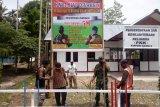 Babinsa Koramil Yapsel bersama warga Kampung Kainui II pasang banner siap divaksin