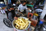 Penyandang disabilitas Osteogenesis Imperfecta Ketut Budiarsa (kanan) bersama kakaknya Nyoman Budiarta melakukan proses pembuatan keripik singkong di kawasan Ubud, Gianyar, Bali, Minggu (21/2/2021). Ketut Budiarsa dan Nyoman Budiarta dibantu keluarganya memproduksi keripik singkong yang dipasarkan secara daring ke berbagai daerah seperti Jakarta, Bandung, Surabaya dan Bali sebagai sumber pendapatan setelah profesi sebelumnya sebagai pelukis serta perajin kerajinan tangan yang dijual di sejumlah toko seni di kawasan pariwisata terdampak pandemi COVID-19. ANTARA FOTO/Fikri Yusuf/nym.