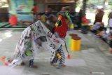 Dua orang anak memainkan barongsai yang terbuat dari barang bekas dan sampah plastik di Kampung Dongeng Ramadhani, Kelurahan Mojoroto, Kota Kediri, Jawa Timur, Minggu (21/2/2021). Pentas tari bertajuk 'Barongsai Sampah' tersebut guna memperingati Hari Peduli Sampah Nasional. Antara Jatim/Prasetia Fauzani/zk