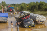 Sejumlah truk terperosok di Jalan Gubernur Sarkawi yang rusak di Kecamatan Sungai Tabuk, Kabupaten Banjar, Kalimantan Selatan, Senin (8/2/2021). Pasca banjir Ruas jalan nasional yang menghubungkan Provinsi Kalimantan Selatan dengan Provinsi Kalimantan Tengah tersebut rusak parah akibatnya aktivitas ekonomi terganggu karena menurut pengakuan sopir truk, mereka harus berjibaku bahkan sampai tiga hari lamanya untuk melintas di jalan yang merupakan akses utama angkutan barang. ANTARA FOTO/Bayu Pratama S./foc.
