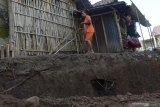 Seorang anak melintas di samping areal tanah yang ambles di Desa Buduran, Wonoasri, Kabupaten Madiun, Jawa Timur, Minggu (21/2/2021). Menurut warga setempat banjir Sungai Jeroan selama beberapa hari terakhir mengakibatkan tanggul sungai putus dan ambles yang diikuti amblesnya areal di sekitar permukiman warga sedalam sekitar dua meter dan panjang sekitar 30 meter. Antara Jatim/Siswowidodo/zk