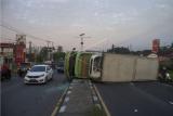 Sejumlah kendaraan melintas di dekat truk pengangkut barang kemasan yang terguling di Jalur Pantura, Desa Cibanggala, Subang, Jawa Barat, Minggu (21/2/2021). Kecelakaan truk tersebut terjadi diduga akibat supir mengantuk sehingga menabrak pembatas jalan dan terbalik menutup badan jalan sehingga jalur lalu lintas pun dialihkan. ANTARA FOTO/M Ibnu Chazar/wsj.