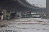 Sejumlah kendaraan terjebak kemacetan saat banjir menggenangi Tol Jakarta Cikampek Km 19 Tambun, Kabupaten Bekasi, Jawa Barat, Sabtu (20/2/2021). Banjir di jalan Tol Jakarta - CIkampek disebabkan luapan sungai Kali Jambe. ANTARA FOTO/ Fm/Arisanto/hp.