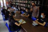 Anggota polisi memberikan pendidikan budi pekerti kepada sejumlah siswa saat kegiatan belajar di Perpustakaan Sabha Widya Sradha, Desa Sumerta Kelod, Denpasar, Bali, Senin (22/2/2021). Perpustakaan desa tersebut aktif memberikan pendidikan nonformal kepada para siswa selama pandemi COVID-19 untuk membentuk karakter dan memotivasi semangat belajar. ANTARA FOTO/Nyoman Hendra Wibowo/nym.