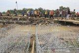Warga bersama petugas gabungan bergotong royong memperbaiki tanggul sungai Cipunagara yang jebol di desa Bongas, Pamanukan, Subang, Jawa Barat, Rabu (24/2/2021). Puluhan warga dibantu personel TNI, BPBD dan LSM bergotong royong memperbaiki tanggul jebol yang menyebabkan banjir di Pamanukan dengan material yang didatangkan oleh dinas PUPR dan BBWS Citarum. ANTARA JABAR/Dedhez Anggara/agr
