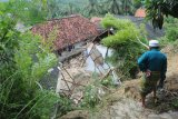 Warga menyaksikan Pesantren An Nidhoniyah yang tertimbun longsor di Desa Bindang, Pamekasan, Jawa Timur, Rabu (25/2/2021). Tanah longsor yang disebabkan hujan deras itu, menimbun asrama pesantren dan menyebabkan lima orang santri putri meninggal dunia serta dua orang mengalami luka berat. Antara Jatim/Saiful Bahri/zk