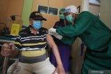 Tenaga kesehatan menyuntikkan vaksin COVID-19 kepada warga lanjut usia di Puskesmas Pakis di Jalan Kembang Kuning Makam, Surabaya, Jawa Timur, Selasa (23/2/2021). Vaksinasi COVID-19 dilakukan kepada warga lanjut usia dan digelar secara bertahap tersebut sebagai upaya penanggulangan pandemi COVID-19. Antara Jatim/Didik/Zk