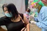 Petugas menyuntikkan vaksin COVID-19 ke lengan kiri salah satu pedagang di Pasar Ngemplak,  Tulungagung, Jawa Timur, Rabu (24/2/2021).  Di daerah ini, selain ASN/TNI/Polri dan kelompok jurnalis, pedagang pasar-pasartradisional yang jumlahnya mencapai 12 ribu lebih menjadi salah satu prioritas vaksinasi tahap 2 karena dinilai rentan terpapar COVID-19. Antara Jatim/Destyan Sujarwoko/zk
