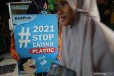 Aktivis lingkungan membentangkan poster saat mengkampanyekan #2021stopmakanplastik di kampung nelayan Kenjeran, Surabaya, Jawa Timur, Kamis (25/2/2021). Aksi yang dilakukan oleh Ecoton, Komunitas Tolak Plastik dan sejumlah mahasiswa tersebut dilakukan untuk mengajak masyarakat tidak membuang sampah plastik sembarangan serta mengurangi penggunaan plastik sekali pakai.  Antara Jatim/Didik/Zk