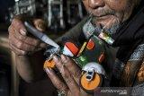 Seorang perajin Ade Syaripudin (67) menyelesaikan produksi miniatur sepeda motor yang terbuat dari limbah kaleng di Sasakgantung, Bandung, Jawa Barat, Jumat (26/2/2021). Perajin memanfaatkan limbah kaleng, plastik dan elektronik di sekitar permukimannya untuk dijadikan kerajinan miniatur sepeda motor dan robot yang dijual dengan harga Rp 15 ribu hingga Rp 150 ribu. ANTARA JABAR/Raisan Al Farisi/agr