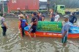 Petugas bawa jenazah pakai perahu di tengah banjir untuk dimakamkan