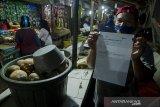 Seorang pedagang menunjukkan bukti vaksinasi COVID-19  usai disuntik di Pasar Sederhana, Bandung, Jawa Barat, Sabtu (27/2/2021). Sedikitnya 200 pedagang di pasar tersebut menerima Vaksin COVID-19  dosis pertama pada pelaksanaan vaksin tahap dua Jawa Barat yang ditujukan bagi lansia, pedagang pasar, ASN,TNI-Polri. ANTARA JABAR/Novrian Arbi/agr