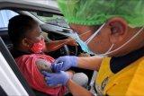 Vaksinator menyuntikkan vaksin COVID-19 kepada pekerja sektor pariwisata yang berada di atas kendaraan saat vaksinasi COVID-19 dengan sistem 'drive thru', di Nusa Dua, Badung, Bali, Minggu (28/2/2021). Layanan vaksinasi dengan sistem 'drive thru' yang dilaksanakan Kementerian Kesehatan berkolaborasi dengan Grab dan Good Doctor tersebut merupakan layanan pertama yang dihadirkan di kawasan Asia Tenggara guna membantu mempercepat pelaksanaan vaksinasi COVID-19 di Indonesia. ANTARA FOTO/Fikri Yusuf/nym.
