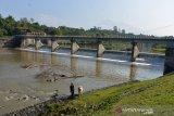 Petani menggembalakan ternaknya di lokasi Irigasi Krueng Aceh, Desa Seunebok, Kecamatan Seulimeum Kabupaten Aceh Besar, Selasa (2/3/2021). Petugas penjaga pintu irigasi di daerah itu, menyatakan Irigasi Krueng Aceh yang berfungsi memenuhi kebutuhan air sawah selama musim kemarau debit air menurun  hingga 70 sentimeter dari kondisi normal 80 sentimeter. ANTARA FOTO/Ampelsa