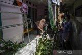 Pengurus  RW membagikan bantuan kepada kerabat warga yang melakukan isolasi mandiri  positif COVID-19 di RW 10 Kampung Pangkalan, Kabupaten Bandung Barat, Jawa Barat, Rabu (3/3/2021). Sedikitnya 39 warga di kawasan tersebut terdata positif COVID-19 usai wisata ziarah ke Pamijahan, Tasikmalaya sehingga kawasan tersebut terpaksa diisolasi dengan diberlakukan PPKM skala mikro. ANTARA JABAR/Novrian Arbi/agr