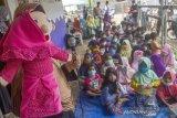 Seorang relawan menghibur anak-anak korban banjir dengan boneka tangan saat