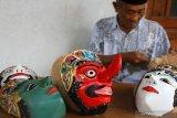 Perajin membuat topeng Panji untuk dijual sebagai suvenir wisata dan sarana pementasan tari di Sanggar Lintang Pandu Sekar, Tumpang, Malang, Jawa Timur, Rabu  (3/3/2021). Perajin topeng Panji setempat mengaku minimnya kunjungan wisatawan dan terbatasnya pementasan tari topeng seiring perpanjangan Pemberlakuan Pembatasan Kegiatan Masyarakat (PPKM) Mikro membuat usahanya sulit untuk pulih. Antara jatim/Ari Bowo Sucipto/zk