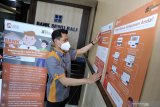 Pegawai Lembaga Penjamin Simpanan (LPS) menempelkan poster panduan bagi nasabah PT Bank Perkreditan Rakyat (BPR) Sewu Bali di Tabanan, Bali, Rabu (3/3/2021). LPS akan melakukan rekonsiliasi dan verifikasi data simpanan dan informasi lainnya untuk proses pembayaran klaim simpanan nasabah dan likuidasi PT BPR Sewu Bali setelah izin usaha BPR tersebut dicabut oleh Otoritas Jasa Keuangan pada tanggal 2 Maret 2021. ANTARA/Naufal Fikri Yusuf