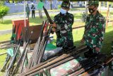 Dua personel TNI-AD Korem 161/Wirasakti Kupang memeriksa sejumlah unit senjata sebelum dimusnahkan di Markas Lantamal VII, Kupang, NTT, Sabtu (6/3/2021). Dua batalyon Satgas Pamtas RI-RDTL Yonarmed 3/105 Tarik dan Yonif Raider Khusus 744/SYB berhasil mengumpulkan 30 pucuk senjata rakitan, empat pucuk senjata TNI, satu pistol rakitan, tiga buah granat, satu buah mortir serta 483 butir peluru tajam yang diperoleh dari warga eks Timor Timur yang memberikan secara sukarela. ANTARA FOTO/Kornelis Kaha/nym.