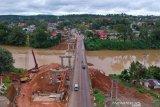 Pekerja menyelesaikan pembangunan Jembatan Merangin 2 di samping Jembatan Merangin, Jalan Lintas Sumatera Jambi-Sumbar, Bangko, Merangin, Jambi, Minggu (7/3/2021). Pembangunan jembatan di atas pertemuan arus Sungai Batang Merangin dan Sungai Batang Mesumai dengan nilai proyek Rp58 miliar dari APBN tersebut ditargetkan selesai dalam tahun ini. ANTARA FOTO/Wahdi Septiawan/rwa.