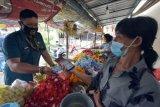 Pedagang melakukan pembayaran menggunakan aplikasi QRIS DOKU saat sosialisasi implementasi solusi layanan perbankan dan cashless society pembayaran e-retribusi di Pasar Banjar, Buleleng, Bali, Senin (8/3/2021). Kegiatan tersebut untuk memudahkan pedagang di pasar tradisional dalam melakukan pembayaran retribusi secara non tunai pada masa pandemi COVID-19. ANTARA FOTO/Nyoman Hendra Wibowo/nym.