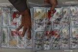 Polisi menunjukkan barang bukti saat ungkap kasus peredaran uang palsu di Polrestabes Surabaya, Jawa Timur, Senin (8/3/2021). Polrestabes Surabaya menangkap IWW (42) dan SMJ (56) atas kasus dugaan mengedarkan uang palsu serta mengamankan barang bukti uang palsu pecahan 100 dolar Amerika Serikat sebanyak 15 ribu lembar. Antara Jatim/Didik Suhartono/zk