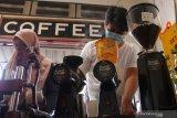 Barista menyeduh kopi untuk diberikan secara gratis dalam peringatan Hari Kopi Nasional di Kedai Klodjen Djaja, Malang, Jawa Timur, Kamis (11/3/2021). Kegiatan tersebut bertujuan memperkenalkan cita rasa kopi khas nusantara antara lain kopi Aceh Gayo, Buleleng dan Arjuna. Antara Jatim/Ari Bowo Sucipto/zk