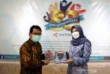 Kepala ANTARA Biro Jawa Timur Slamet Hadi Purnomo (kiri) memberikan buku karya jurnalistik pewarta ANTARA Jatim kepada Bupati Banyuwangi Ipuk Fiestiandani Azwar Anas (kanan) saat berkunjung ke Kantor ANTARA Biro Jatim di Surabaya, Senin (15/3/2021). Kunjungan tersebut dalam rangka silaturahim sekaligus memperkenalkan visi dan misi bupati periode 2021-2024. (ANTARA Jatim/Naufal Ammar Imaduddin/SHP)